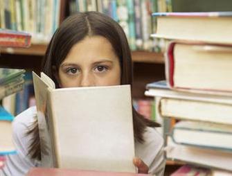 Отличница сидит за книгами в библиотеке