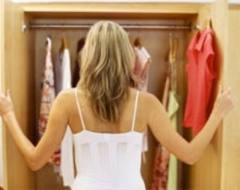Девушка выбирает платье в гардеробе