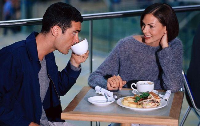 Мужчина с женщиной в кафе за столиком пьют кофе