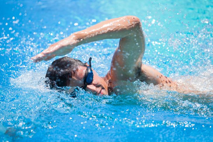 Мужчина плывет кролем в бассейне