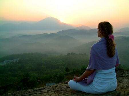 Девушка медитирует на рассвете