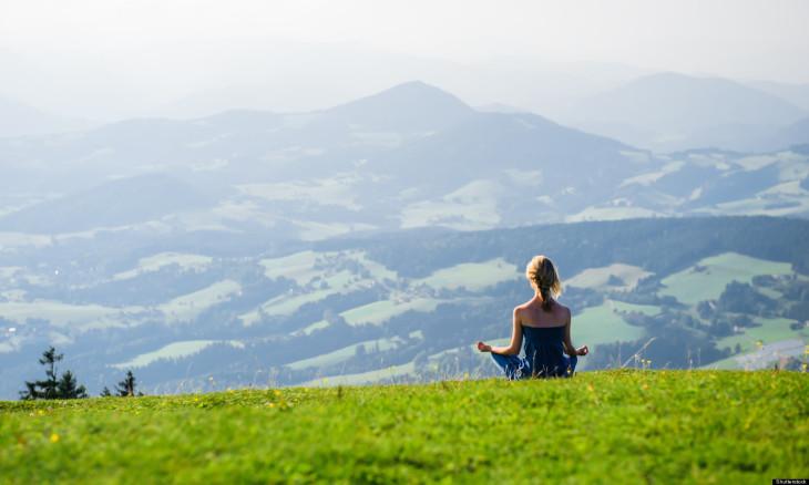 Девушка медитирует в горах